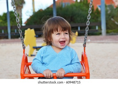 The beautiful little boy in blue sweater  laughs cheerfully at a red swing
