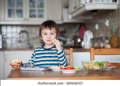 Beautiful little boy, eating sandwich at home, playing on tablet, vegetables on the table