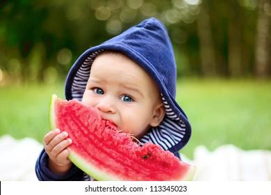 beautiful little boy eats ripe watermelon on the nature