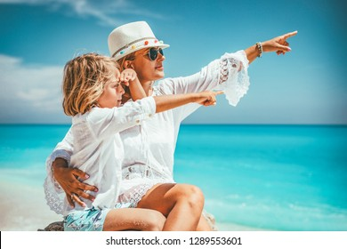 Beautiful little boy enjoying with his mother on the beach rock. They are pointing something.