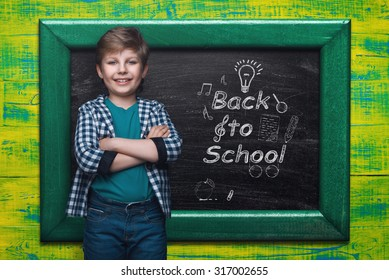 Beautiful little boy on the background of the school board. Empty space for text. School lessons. Back to school. Colored backgrounds