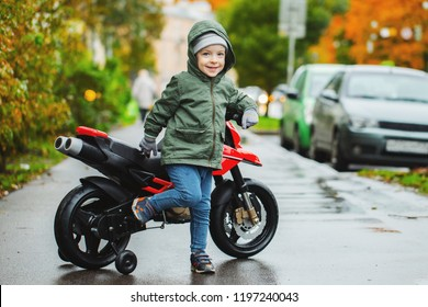 A beautiful little boy posing at his children's red motorcycle. The concept of teaching children to motor vehicles from an early age.