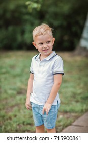 A beautiful little boy is walking outdoors during the summer holidays