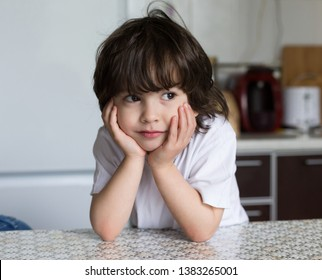 Beautiful little brunet boy, has happy fun smile face, pretty brown eyes, long hair, sitting in kitchen. Child portrait. Family kids concept. Concept beauty people.