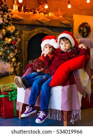 Beautiful little brunet boys, has happy serious face, brown eyes, red Christmas hat Santa Claus. Portrait family holiday. Close up. Winter background. Blood brothers. Night light