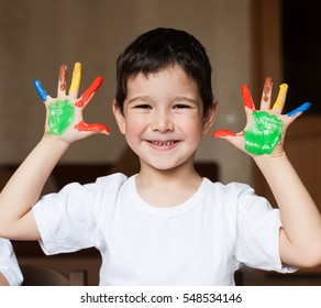 Beautiful little brunet hair boy, has happy fun smiling face, brown eyes, white t-shirt. Painted in skin hands. Child portrait. Creative concept. Water colors.  Close up.