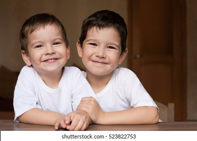 Beautiful little brunet hair boys, has happy fun smiling face, brown eyes, white t-shirt. Child portrait. Creative concept. Close up. Blood brothers.