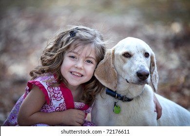 Beautiful little brunette girl hugging a friendly dog