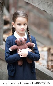 Beautiful little brunette girl with with pigtails, dressed in dark blue standing near mystic abandoned building with gothic stairs and holding handmade bear toy. Halloween horror, ghost or spirit