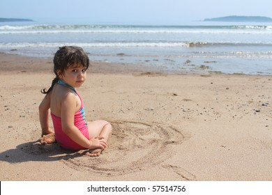Beautiful little brunette girl in pink bathing suit sitting in the sand at New River beach, New Brunswick, Canada