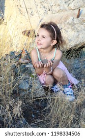 Beautiful little brunnette girl playing amongst ruins