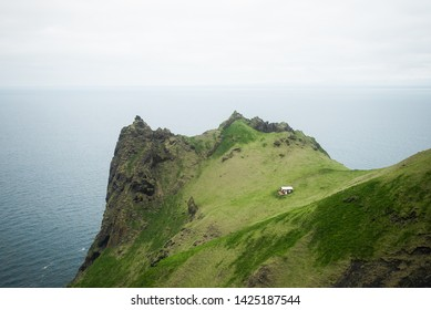 Beautiful little cabin or shelter isolated from the rest of the world and located on a spectacularly steep and oddly shaped rocky hill covered with contrasted green grass and moss on an overcast day.