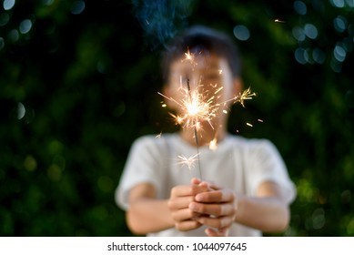 Beautiful little candle fireworks in a hand of young Asian Thai boy.