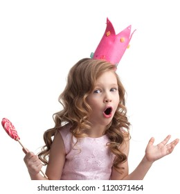 Beautiful little candy princess girl in crown holding big pink heart lollipop
