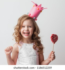 Beautiful little candy princess girl in crown holding big pink heart shaped lollipop and smiling