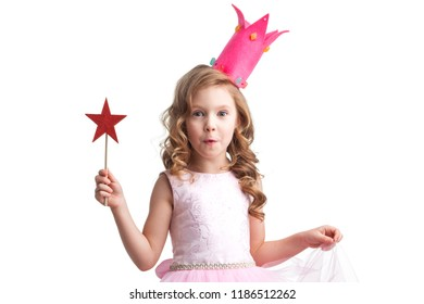 Beautiful little candy princess girl in crown holding star shaped magic wand and making a wish