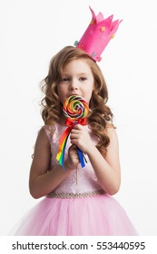 Beautiful little candy princess girl in crown holding big lollipop isolated on white