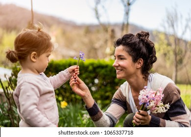 Beautiful little child baby girl giving flower to gorgeous mom