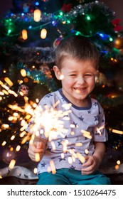 Beautiful Little child holding burning sparkler on New Year's Eve, bengal fire. There is a background with multi colored lights. Happy boy holding sparklers on blurred christmas background