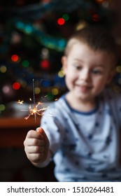 Beautiful Little child holding burning sparkler on New Year's Eve, bengal fire. There is a background with multi colored lights.