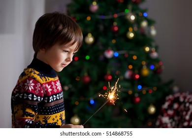 Beautiful Little child holding burning sparkler on New Year's Eve, casual clothing, bengal fire