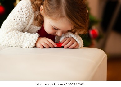 Beautiful little child plays with little red toy car.