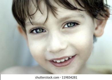 Beautiful little child with wet hair smiling close up portrait