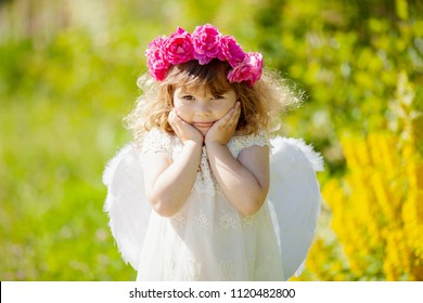 Beautiful little curly blonde Angel girl with wreath made of red roses smiles and teases. Summer day, flowers at the background. Concept of angelic child with a bad temper