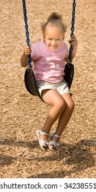 Beautiful little ethnic girl on swing with a smile wearing a pink shirt, shorts and sandals. The scene was set against a playground wood chip mulch textured background.