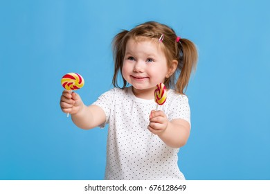 Beautiful little female child holding huge lollipop spiral candy smiling happy isolated on blue background.