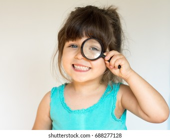 Beautiful little four years girl looking through a magnifying glass, preschool kids, education