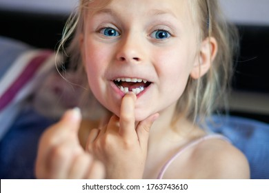 A beautiful little girl of 6-7 years old lost the first milk tooth. Loss of primary teeth, replacement of teeth with permanent ones. Children's dentistry. Beautiful child teeth