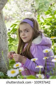 Beautiful little  girl  among chamomiles in a garden