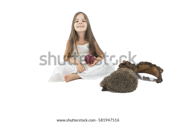 Beautiful little girl with apple in her hand beside hedgehogs