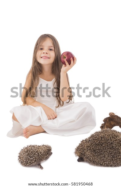 Beautiful little girl with  apple in her hand beside family of hedgehogs