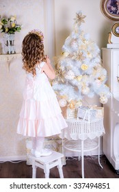 beautiful little girl back to the camera is decorated with a Christmas tree standing on a chair . New Year
