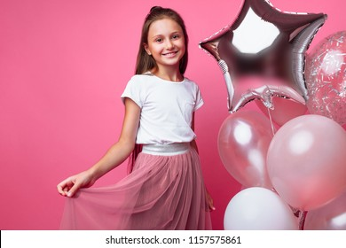 Beautiful little girl, with balls on pink background