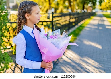 Beautiful little girl with big bouquet of flowers on day of knowledge ( beginning of the school year) near the school.