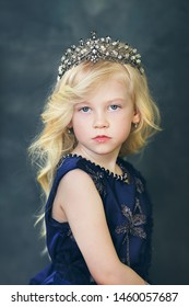 beautiful little girl with blond hair dressed in dark blue dress and with crown on her head