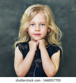 beautiful little girl with blond hair over dark background gesture