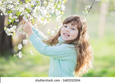 Beautiful little girl in blooming apple tree garden, sunny spring day