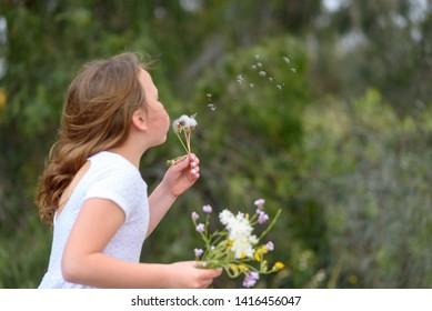 Beautiful little girl blowing dandelion. Portrait adorable little kid holding bouquet of wild flowers. Summer or Autumn. Harvest. Shavuot.