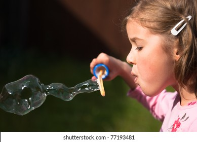 Beautiful little girl blowing an elaborate giant bubble