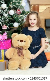 Beautiful little girl in a blue dress is hugging a large Teddy bear . Girl sitting on the floor.
