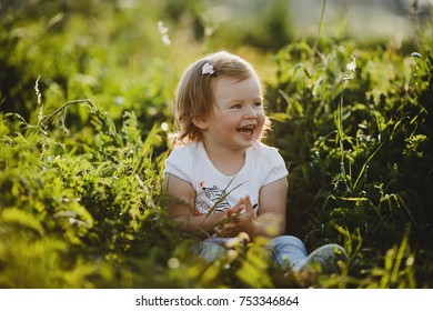 Beautiful little girl in blue jeans and white t-shirt sits on a green grass