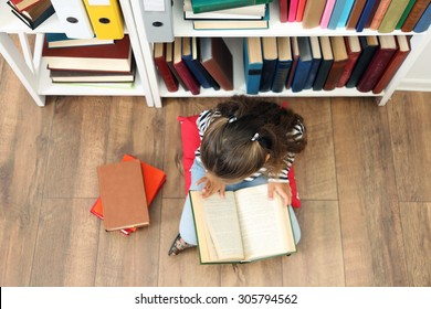 Beautiful little girl with books sitting on floor in library