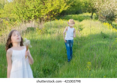 Beautiful little girl and boy collects dandelions in the yard