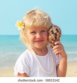 beautiful little girl by the sea with plumeria in hair