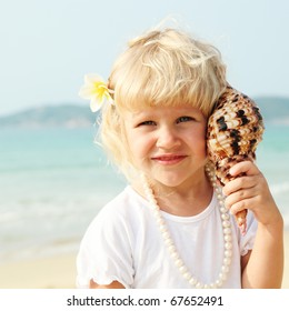 beautiful little girl by the sea with frangipani in hair