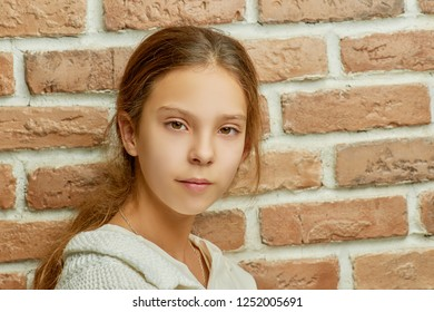 Beautiful little girl with  calm look near  brick wall.